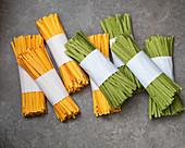 Ungekochte gelbe und grüne Bandnudeln in Bündeln