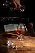 Cognac aus Karaffe in Glas gießen