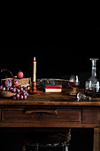 Wooden table with glass of cognac and decanter, candle and grapes