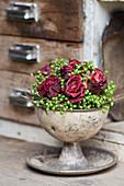 Gesteck aus getrockneten Rosenblüten und unreifen Beeren