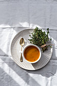 Pumpkin soup in bowl with bunch of herbs