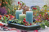 Kerzen auf hellblauer Holzschale, Zweige mit Schlehen und Hagebutten als Dekoration