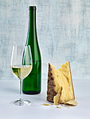 A glass and a bottle of white wine next to a piece of hard cheese