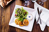 Potato and vegetable fritters with a colourful salad and yoghurt sauce