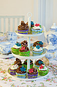 Cupcakes with colorful muffin liners and sugar flowers on a three-tiered dessert stand