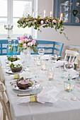 Kronleuchter mit Blumenkranz überm festlich gedeckten Tisch
