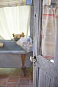 Offene Tür mit Fenster und Patina, Blick ins nostalgische Bad