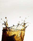 Ice cube falling into a glass of cola
