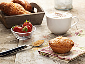 Italienisches Frühstück mit Gebäck, Kaffee und Erdbeeeren