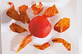 Dried tomato skin next to a peeled tomato