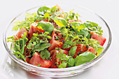 Tomato salad with herbs on a glass plate