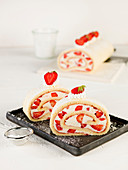 Strawberry Swiss rolls, two slices on a serving platter