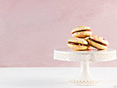 Whoopie pies with colourful sugar sprinkles on a cake stand