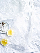 Weißer Papieruntergrund mit Salz und Pfeffer, Zitrone und Gabeln
