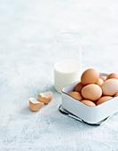 Frische braune Eier und ein Glas Milch