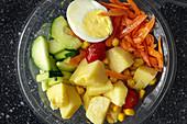 Gemüse mit gekochtem Ei im Plastikbehälter zum Mitnehmen