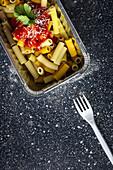 Makkaroni mit Ketchup und Käse im Behälter zum Mitnehmen