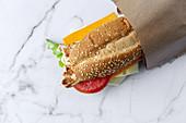 Sandwich mit Käse und Gemüse in Papiertüte zum Mitnehmen