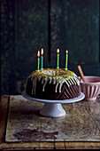 Chocolate Bundt cake with a pistachio glaze and four burning candles