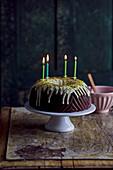 Schokoladen-Gugelhupf mit Pistazienglasur und vier brennenden Kerzen