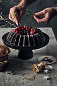 A chocolate Bundt cake with winter decorations on a cake stand