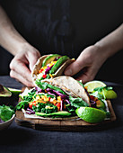 Vegetarian tacos with kale, lime, avocado, taco sauce, cilantro, and bell pepper