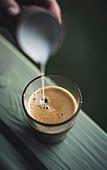 Milch in ein Glas mit Kaffee gießen