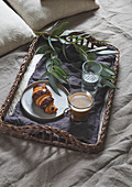 Breakfast in bed - Wicker tray with coffee and croissant on a linen bed