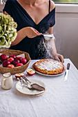 Hausgemachten Apfelkuchen mit Puderzucker bestreuen