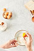 Frauenhände schlagen Ei in eine Rührschüssel auf