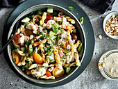Veganer Nudelsalat mit bunten Tomaten, Lauchzwiebeln und Erdnüssen