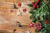 Fir tree branches, red berries and stars over wooden background
