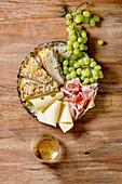 Antipasti mit weißer sizilianischer Focaccia, Prosciutto, Käse und Trauben (Italien)