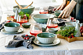 Rustic Christmas table setting with craft ceramic tableware, plates and bowls