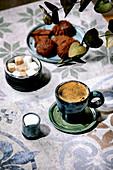 Eine Tasse türkischer schwarzer Kaffee mit Milch, Zuckerwürfeln und Keksen