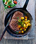 Rump steak with rosemary potatoes in a pan