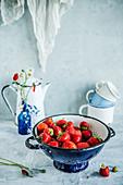 Fresh strawberries in a navy blue colander