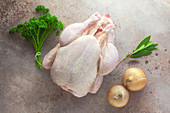 Ingredients for chicken broth: a whole raw chicken, herbs and onions