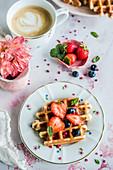 Waffeln mit Erdbeeren und Blaubeeren zur Tasse Kaffee