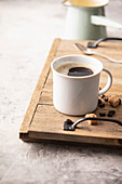 A cup of black coffee with sugar cubes
