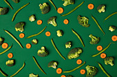 Broccoli, carrots and green beans on green background