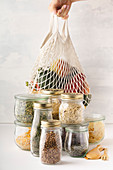Fruits and vegetables in reusable bags and glass jars with pasta, lentils, beans, rice, dry herbs