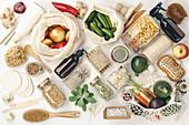 Obst und Gemüse in wieder verwendbaren Beuteln und verschiedene Vorratsgläser mit Lebensmitteln