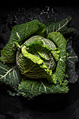 Whole head of green cabbage over black background