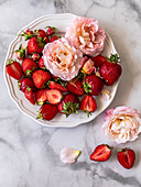 Strawberries and roses on plates