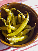 Several hot peppers in a clay dish