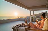 Woman enjoying white wine and sunset ocean view