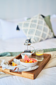 Grapefruit and coffee breakfast tray on morning bed