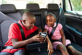 Brother and sister using smart phone