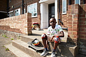 Portrait confident boy with skateboard on front stoop